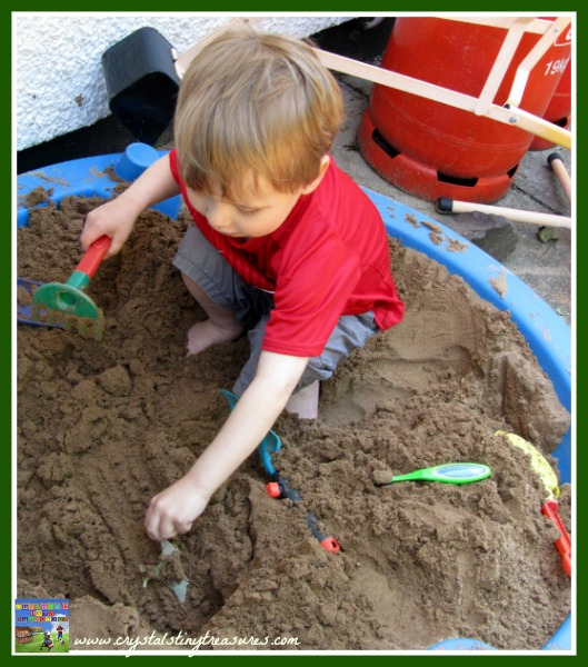 Finding treasure in the sandbox, learning about dinos, fun math game for the sandbox, photo