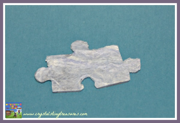covering a puzzle piece with paper, crafts from jigsaw puzzles, photo