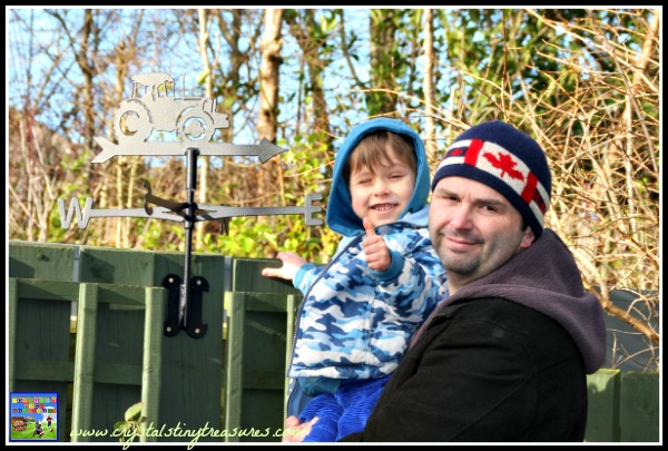 Tractor weathervane installation success, thumbs up for teamwork, ready for a windy day, photo