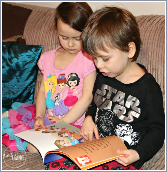 Big brother reading The Golden Rule book to his little sister at CastleViewAcademy
