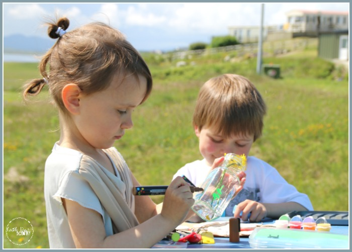 Painting a glass jar to create a simple flower vase while Castle View Academy homeschool is camping