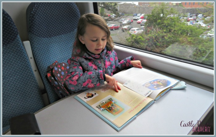 Reading All About Japan on the train helps the time pass for Castle View Academy homeschool