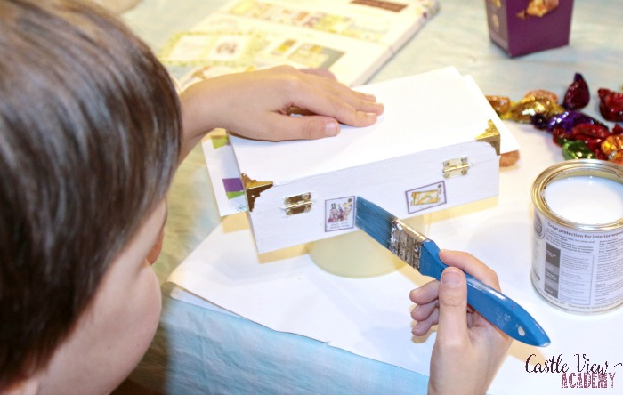 Decorating a wooden box to turn it into a treasure box gift at Castle View Academy