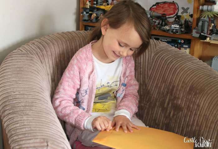 Opening an envelope to reveal Angel Friends at Castle View Academy homeschool