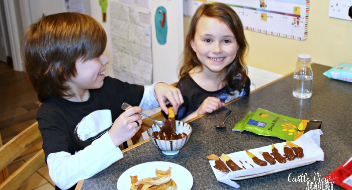 Dipping dried mango into chocolate at Castle View Academy homeschool